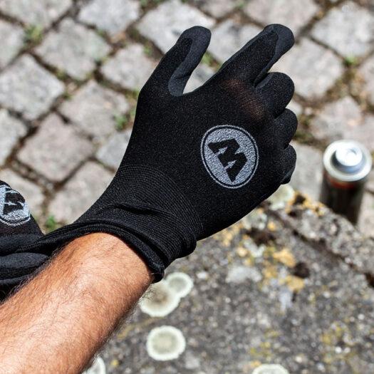 Sfeerbeeld van handen die de Molotow beschermende handschoenen dragen en er staat een fles spray paint op de grond. Molotow bescherming handschoenen vooraanzicht in het zwart/ donkergrijs. De protective gloves geven optimale bescherming en zijn perfect voor het gebruik bij graffiti en streetart, omdat ze de handen beschermen tegen spray paint.